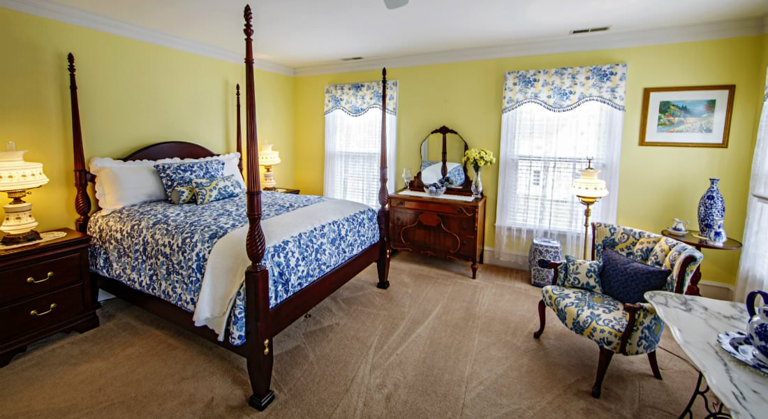 A four post wooden bedframe with blue and white patterned comforter, furniture and draperies.