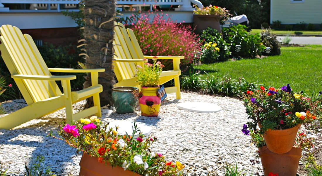 Two yellow Adirondack chairs on a crushed shell ground cover amidst flowers and the lawn.