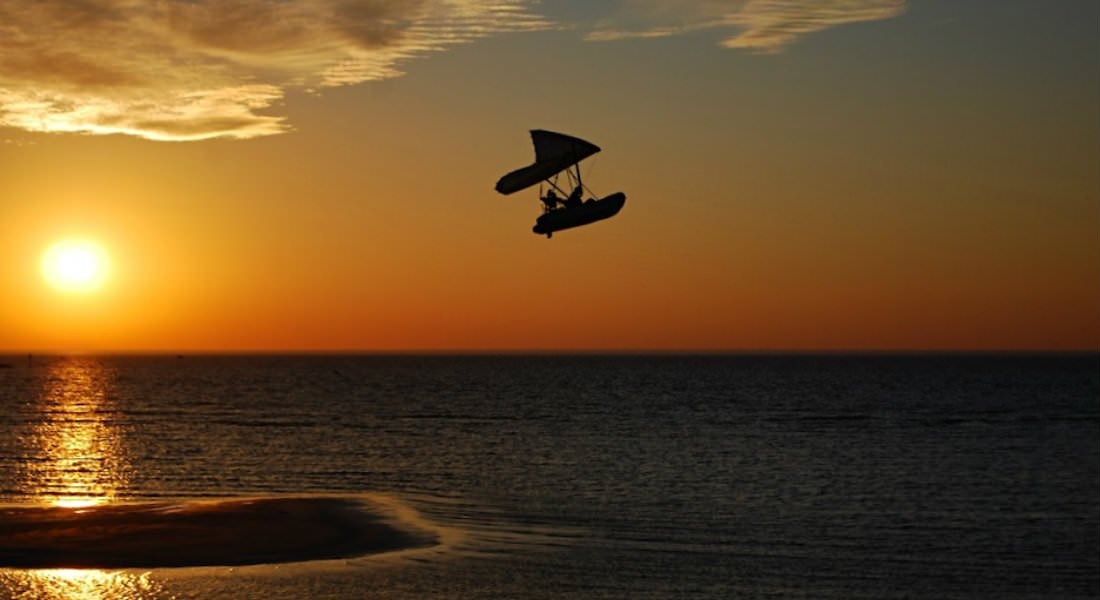 A silhouetted windsurfer catches air over the Bay with a golden sunset in the background.