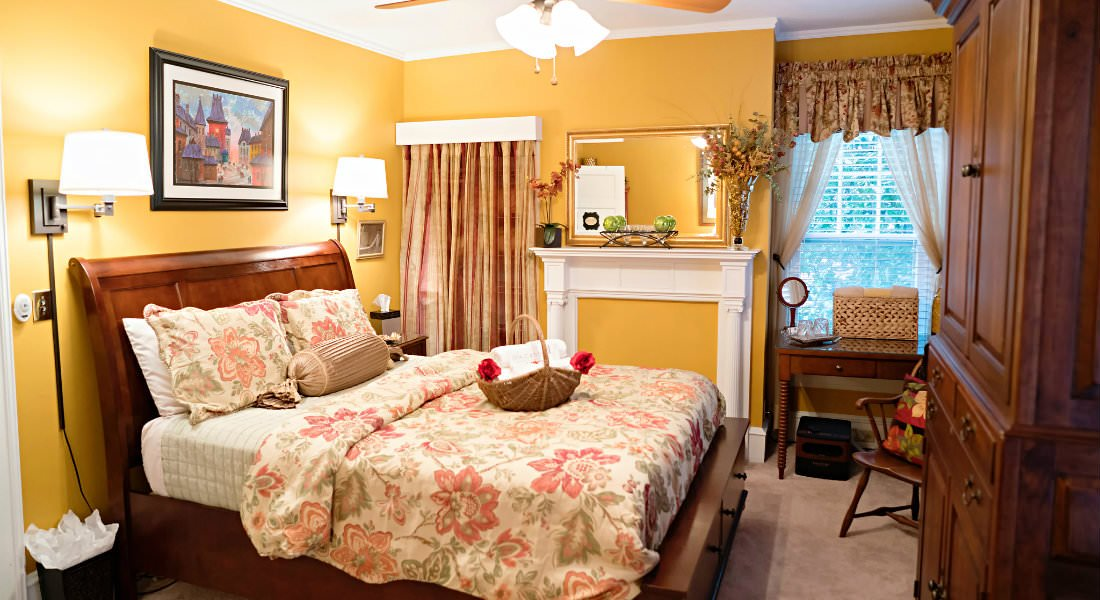 A bed with beige and floral print comforter and pillows, beige carpet and yellow walls.