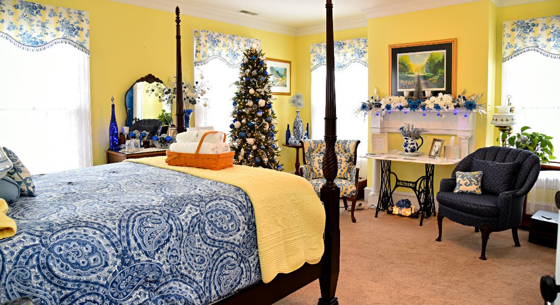 A four-post wooden bedframe and bed with yellow walls and blue and white holiday decorations.