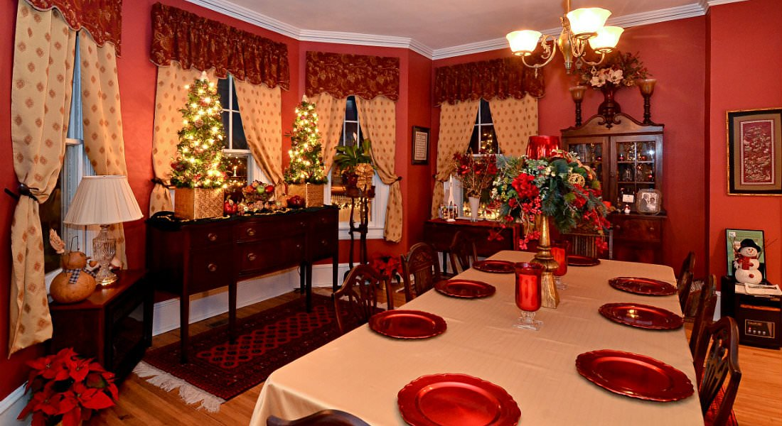 The dining room table is set with eight red plates with cranberry red walls.