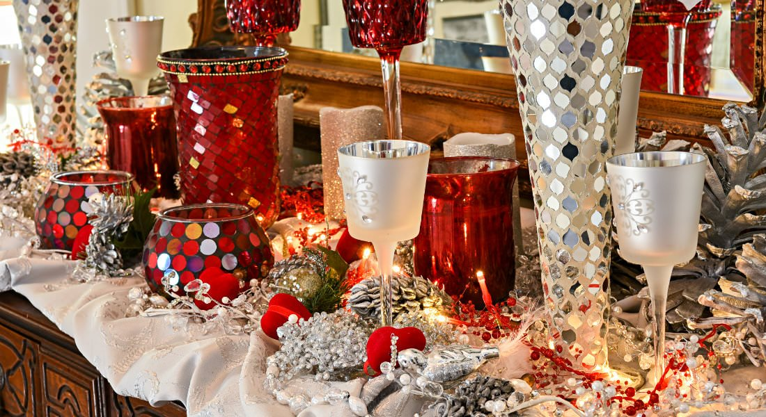 Silver and red glasses, votives and vases sit on an ivory white cloth on wooden furniture.
