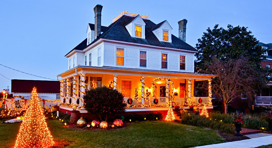 The Inn aglow with golden interior lights, the front porch posts wrapped in festive lighting.