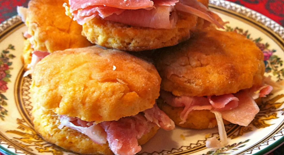 Sweet potato biscuit and Virginia ham sandwiches rest on a floral print plate on a red tablecloth.