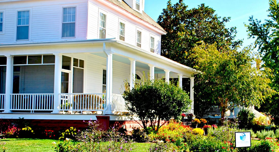 The siding a porch of the Inn glows bright white in the sun behind the lush, green lawn.