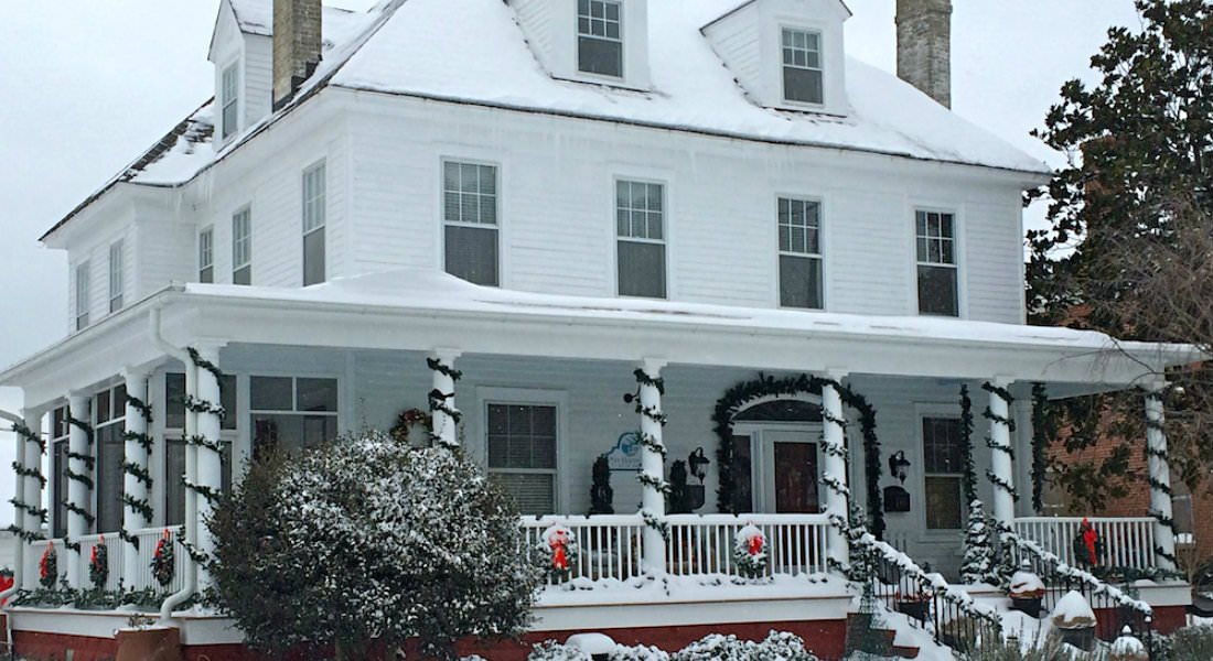The roof of the Inn is covered in fresh, white snow, strand of garland roped around the porch posts.