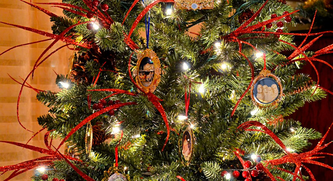 Decorations and red streamers hang from the branches of a green Christmas tree strung with white lights.