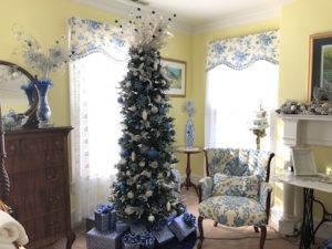 A slender, green Christmas tree decorated with blue and white bulbs and white lights.