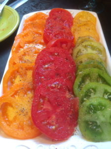 Red, green, and yellow sliced tomatoes on a plate