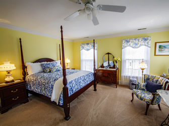 spacious room decorated in Bright and colorful shades of cobalt blue and sunny yellow with a 4 poster bed
