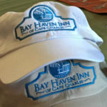A white hat and a beige hat with blue logos and the text: Bay Haven Inn of Cape Charles.