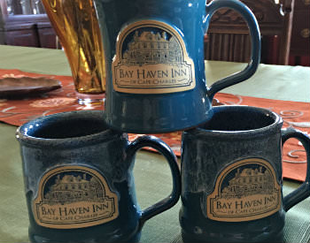 A stack of three blue coffee mugs with beige logos and the text: Bay Haven Inn of Cape Charles.