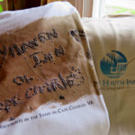 A white t-shirt with a sandy beach and the text: Bay Haven Inn of Cape Charles.