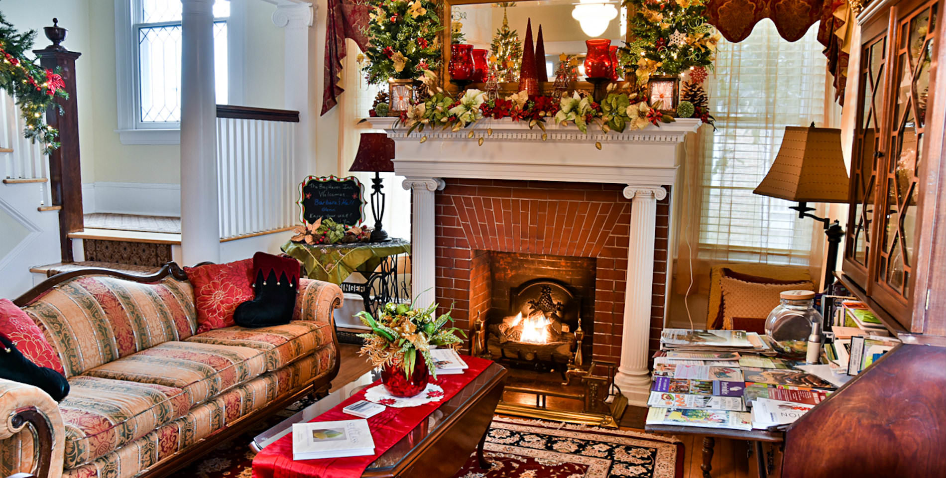 A sitting area adorned with green and yellow leaves with a red brick fireplace and a table covered with magazines.