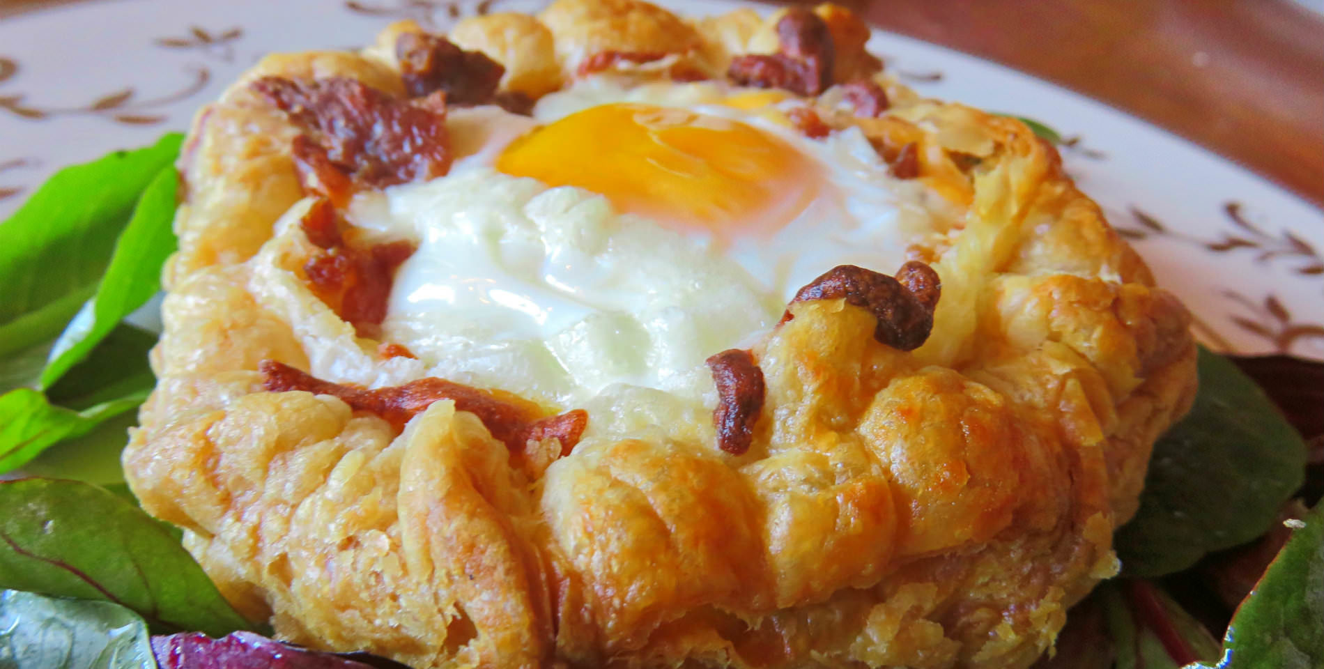 A sunny-side up egg rests in a golden brown flake pastry in a bed of greens.