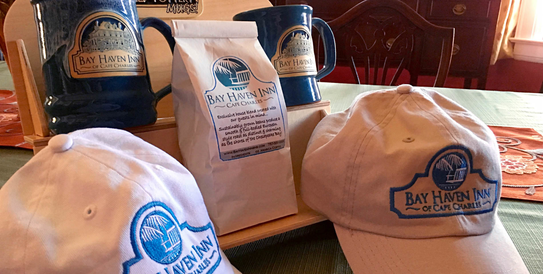 White hats, blue mugs and white bags of coffee with the text: Bay Haven Inn, Cape Charles.