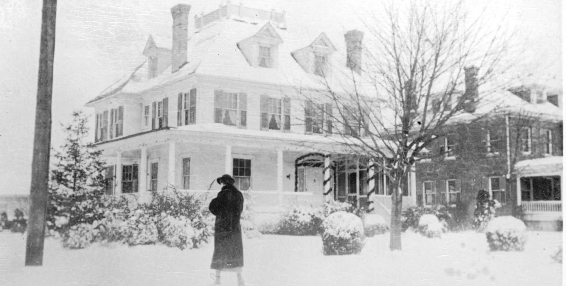 A woman in a black hat and long coat walks toward the Inn during a snowstorm.