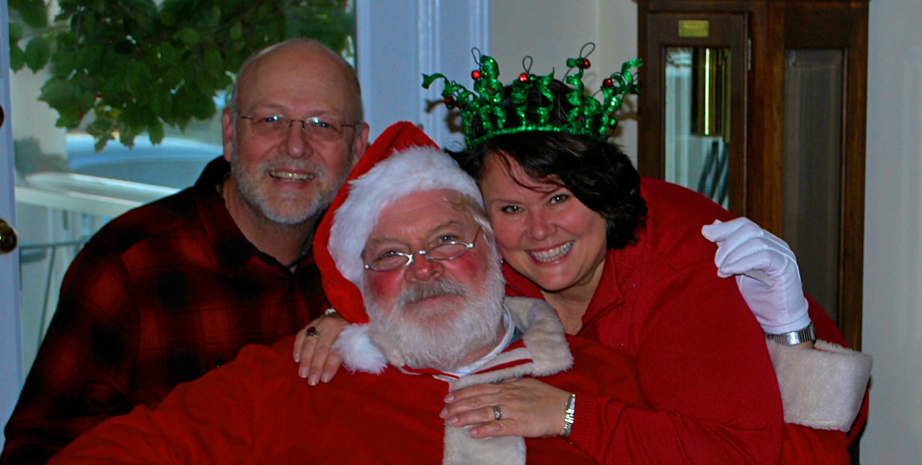 The Innkeepers, Tammy and Jim, smile with a red and white capped and white bearded Santa Claus.
