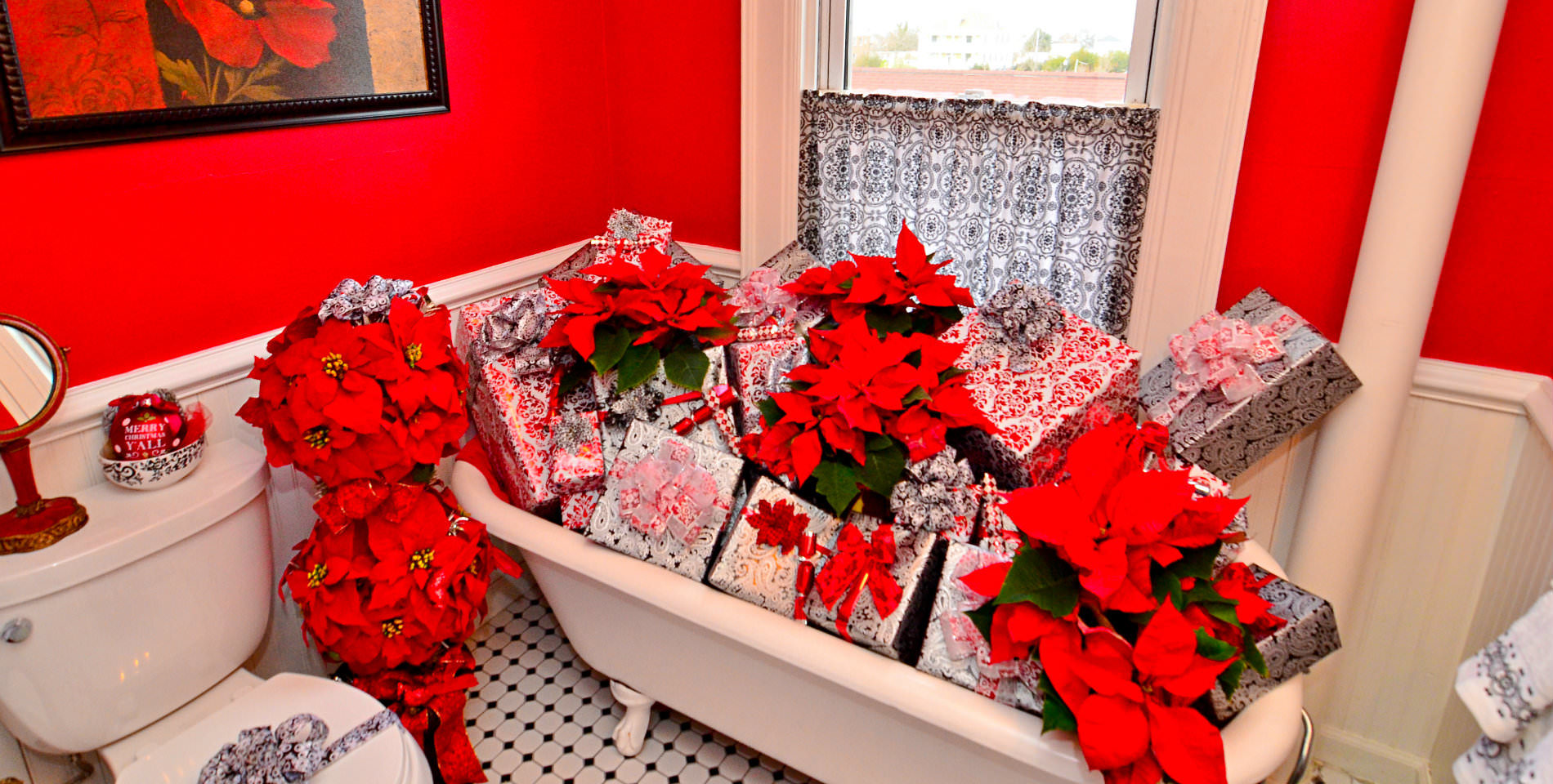 A dozen red poinsettias rest on multiple wrapped and bowed holiday gifts in a white clawfoot tub.