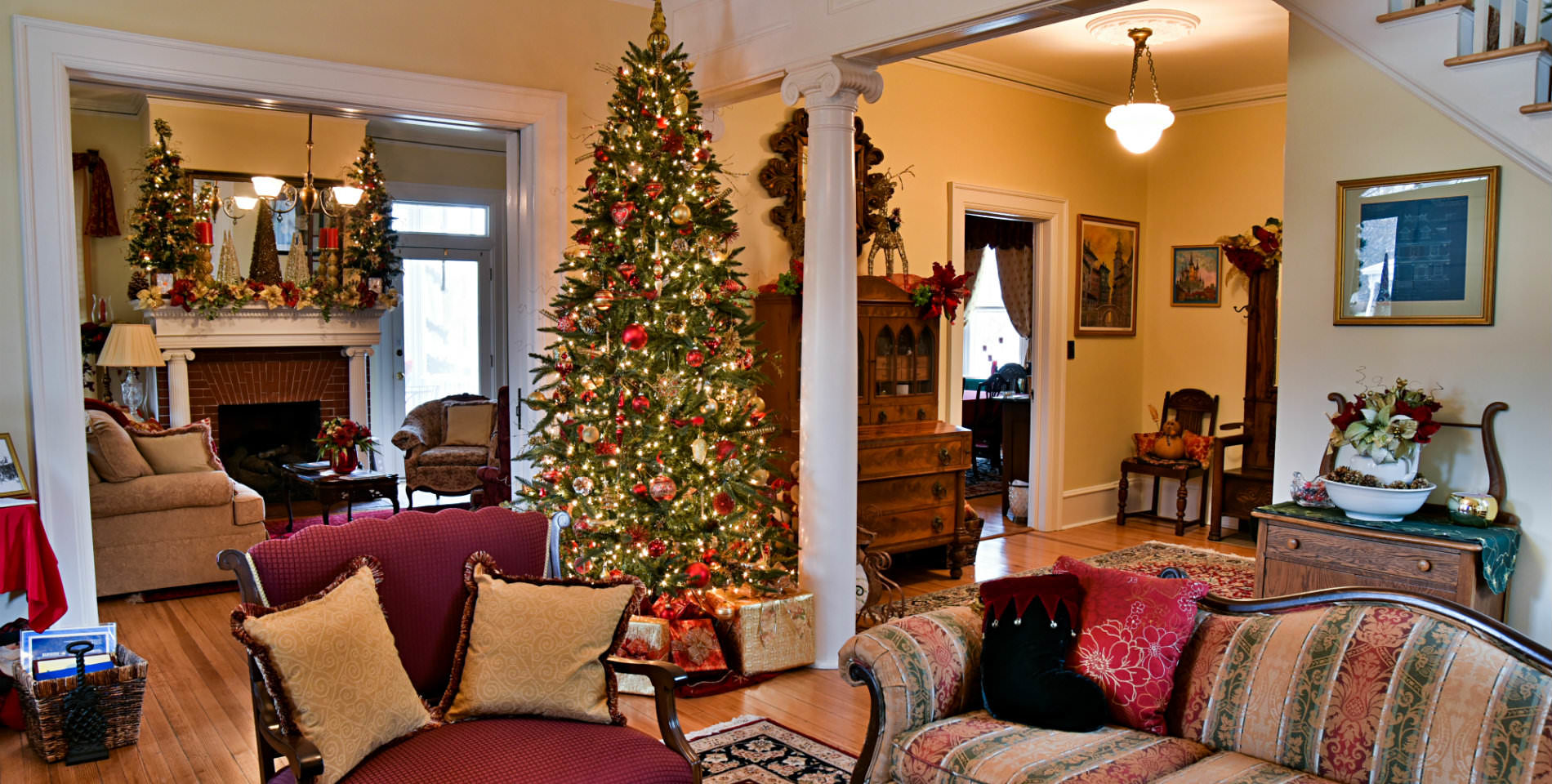A couch and a chair with throw pillows sit before a green Christmas trees decorated with red and gold bulbs.