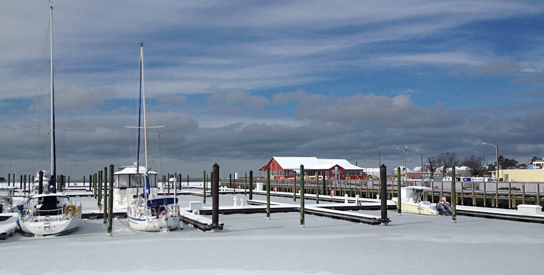 Sailboats rest at the wooden docks, a fine layer of white snow lays on the iced over Bay.