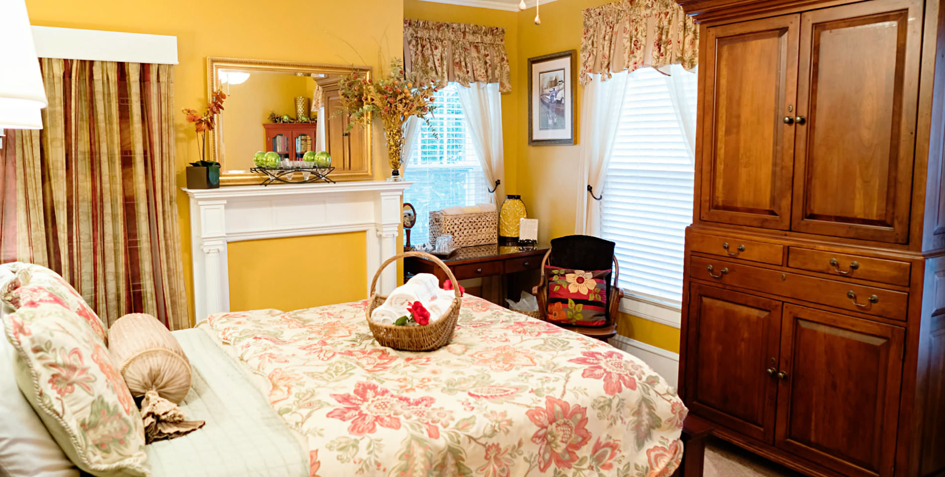 A bed with a beige and floral print comforter with white horizontal blinds in the windows and yellow walls.