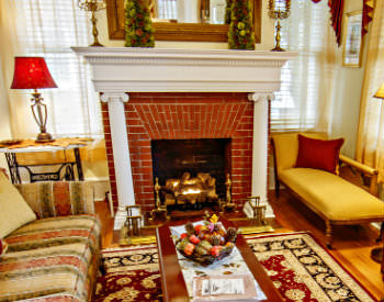 A couch and a chair near a red brick fireplace with a white posted mantle.