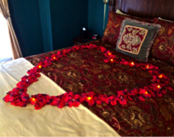 Red rose petals rest in the shape of a large heart on the comforter of a bed.
