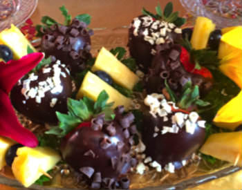 Dark chocolate covered strawberries with green leaves sit in a glass bowl on a table.