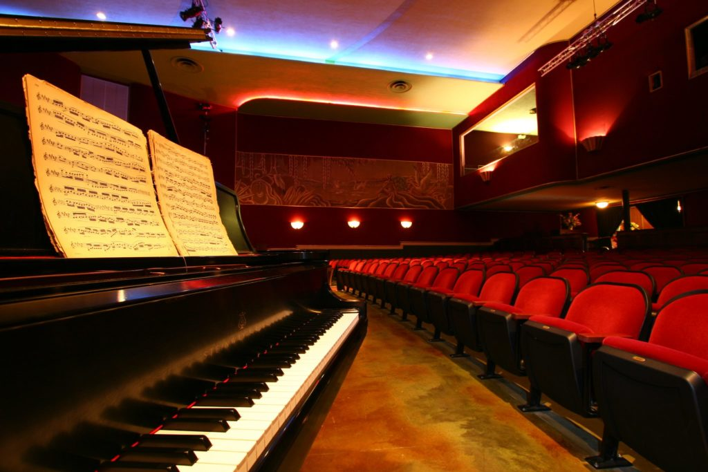 piano and plush red theater seats
