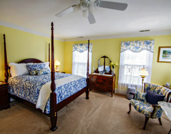 A bed with a blue and white patterned comforter and pillows with beige carpet and yellow walls in the Alyce Wilson room.