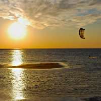 A parasailer glides over the blue and black water of the Bay with a golden sky behind it.