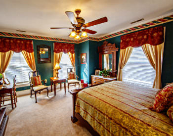 A bed with a gold and red striped comforter with beige carpet and green walls in the James Wilson room.