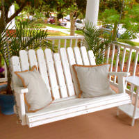 A white wooden rocker with two gray pillows on the front porch before two potted palms.