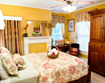 A bed with a beige and floral print comforter and pillows and yellow walls in the Virginia Wilson room.