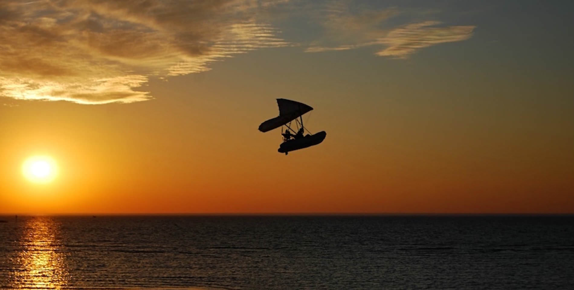 A silhoutetted windsurfer catches air above the Bay with a golden sunsetin the background.