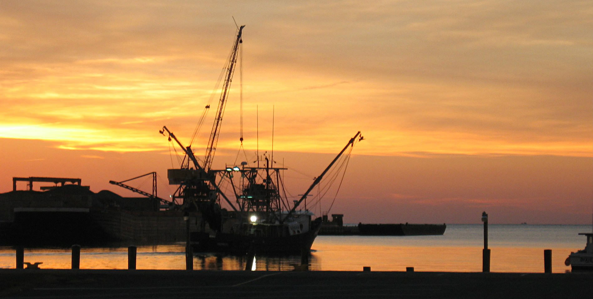 A large crabbing vessel silhouetted near the dock on the Bay with a red and golden sunset in the background.