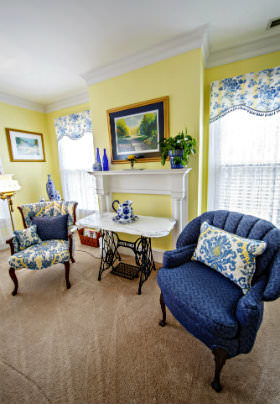 Two blue chairs in a sitting area with beige carpet and yellow walls.
