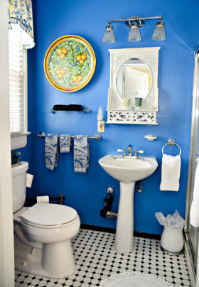 The white porcelain sink and toilet in the bathroom with blue walls.