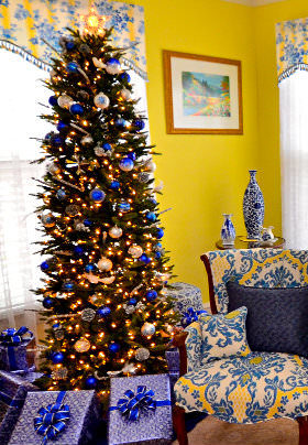 A Christmas tree with blue and white decorations stands above wrapped presents.