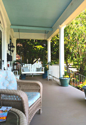 A wicker chair with a light blue cushion sits before a white wooden rocker for two on the front porch of the Inn.