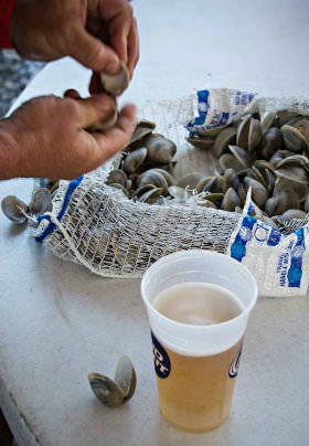 A man shucks mussels from a white basket near a plastic cup of golden beer on the white table.