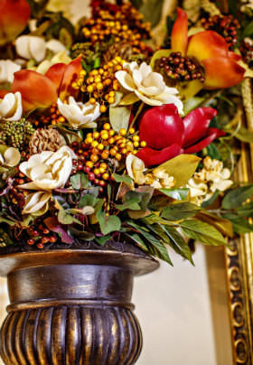 Red and white flowers, yellow berries and green leaves in a brown vase.