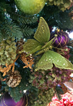 A green decorative butterfly rests on a green trees amidst purple bulbs.