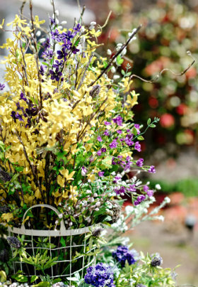 A white wire basket with handles hold a bouquet of yellow, purple and white flowers.
