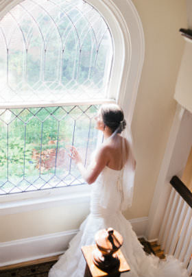 A bride in her white dress stands in the stairwell before a window overlooking the garden.
