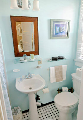 The white porcelain toilet and sink in the bathroom with light, sea foam green walls.