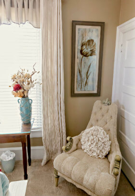 A plush beige chair with a throw pillow near a white closet door and a vase filled with flowers.