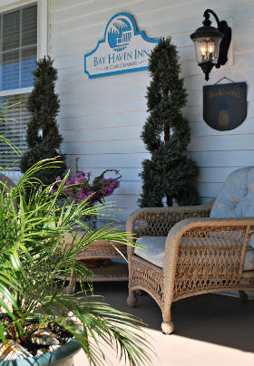 A wicker chair with a light blue cushion near two small pines and a green potted palm on the porch.